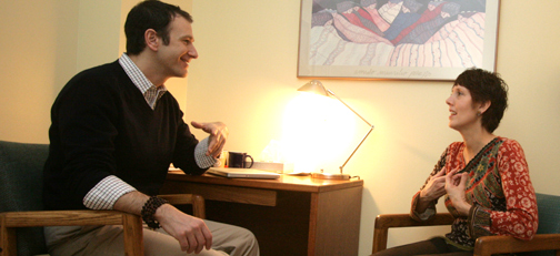 A male psychologist talks to a female patient.