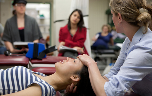 A professor demonstrates a physical medicine technique to students.