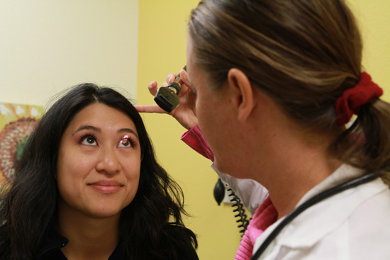 Doctor inspects patient eyes at free health screening