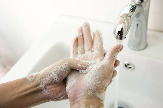 Washing hands in soapy water.