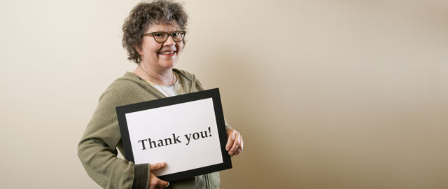 "A happy patient holds a sign that reads ""Thank You"""