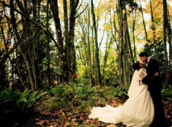 A bride and groom kiss in the woods adjacent to Bastyr.
