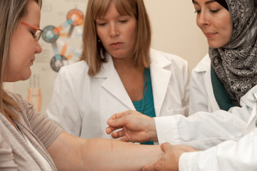Students learn acupuncture techniques on a woman's arm