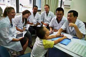 Students and a pediatrics specialist meet a patient at Chengdu University.