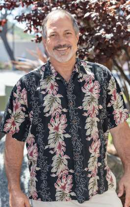 Stu standing and smiling in floral short sleeve shirt