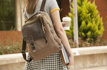 student walking with backpack and cup of coffee