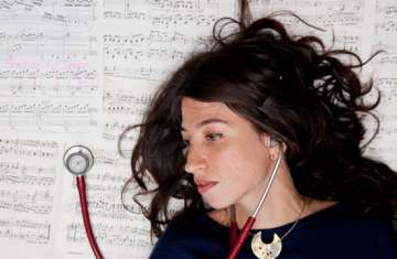 Student Debbie Miller wears stethoscope beside sheet music