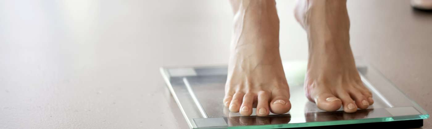 weighing self on glass scale
