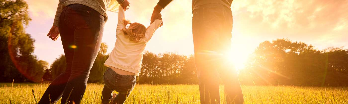 family plays in grass with sun shining