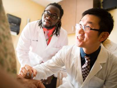 Students smiling and performing acupuncture on patient