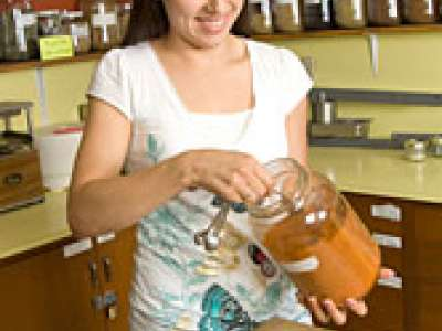 girl reaching into jar of herbs