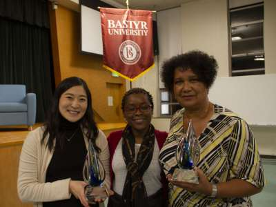 Bastyr students and DEI Associate Vice President holding awards for Speaker Series