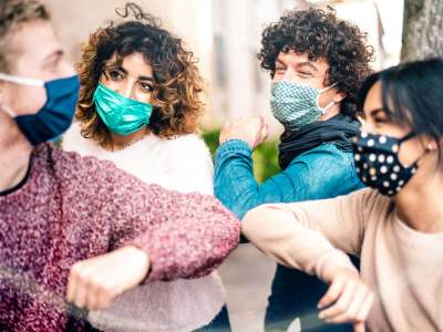 group of four young people elbow bumping with masks on