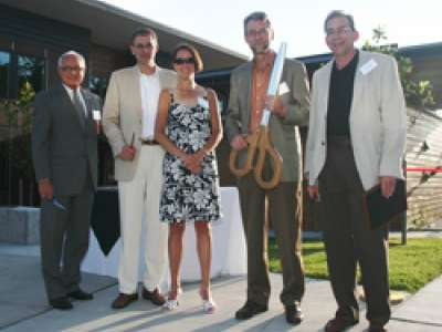 Bastyr donors posing with a giant pair of scissors