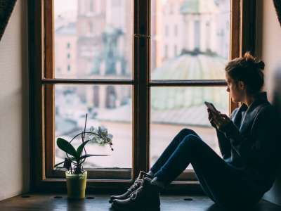woman sitting at window on her phone