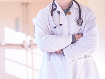 Doctor in white coat standing with arms crossed with stethoscope around neck