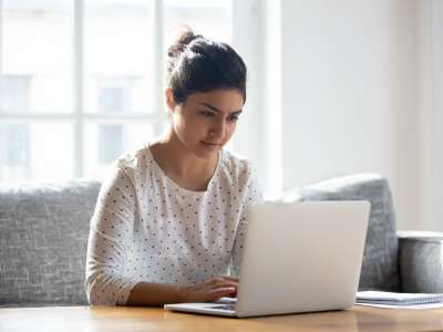 Woman sitting at laptop in sunny room