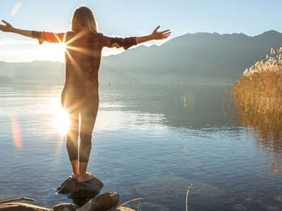 woman looking at rise rise at lake with arms open laterally