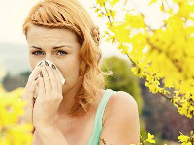 Woman blowing her nose with spring flowers in the background.