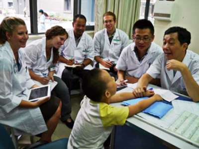 Students and a pediatrician meet with a child.