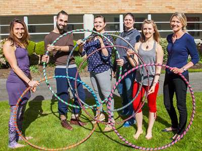 Bastyr undergraduate students standing with hula hoops.