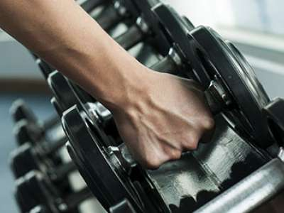 person picking up weights in gym