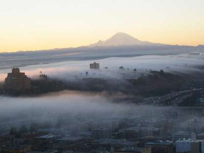 Fog surrounds Seattle with Mt. Rainier in the background.