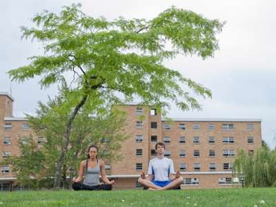 Two students sit in lotus position