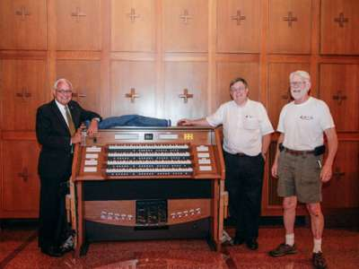 Organ installers and president standing around new organ for chapel