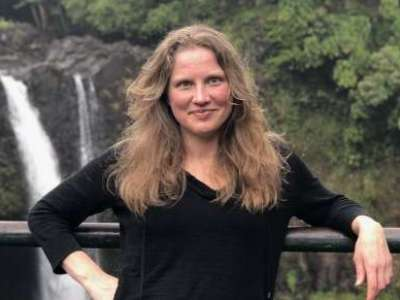 Laurie Mischley in front of waterfall in nature