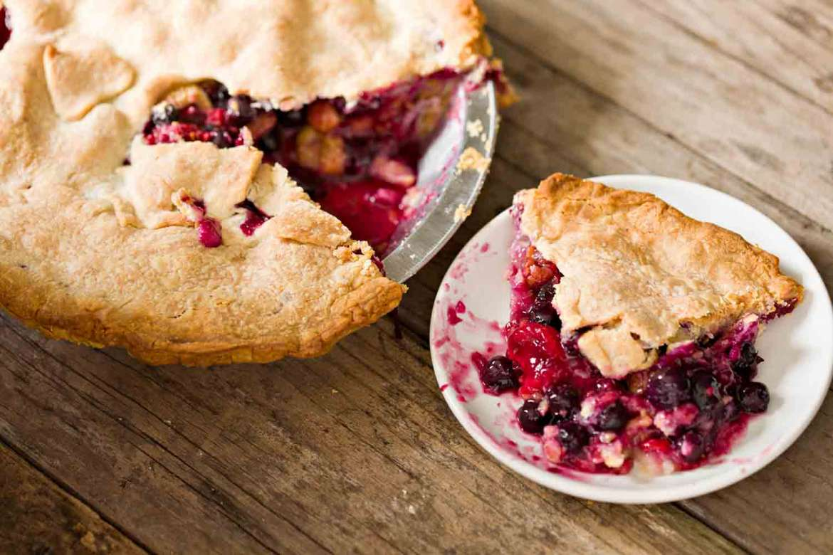 baking pan of berry pie and ready served plate of pie
