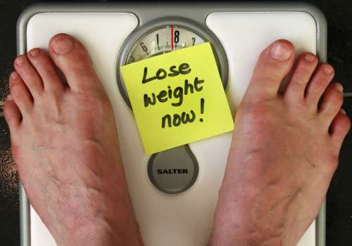 """Scale with sign, """"Lose weight now!"""""""