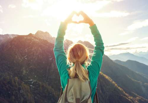woman on mountain making a heart with hands