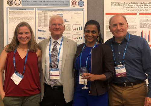 Faculty standing in front of research posters at AIHM Conference