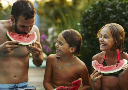 Dad eating watermelon with children by the pool