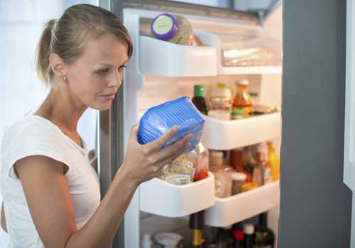 Woman in front of refrigerator inspecting a package of produce.