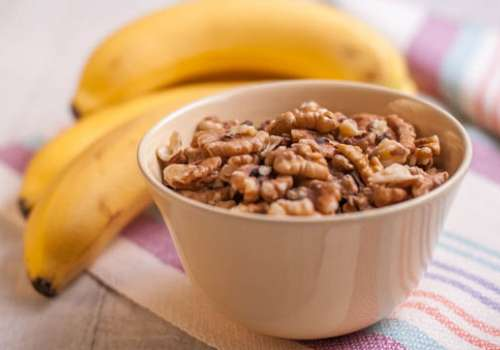 A bowl of walnuts and a bunch of bananas on a table