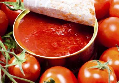 An opened can reveals tomato sauce.