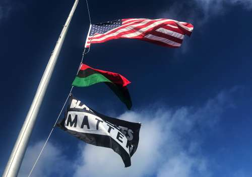 American flag, Black Liberation Flag and Black Lives Matter Flag In Column On Pole
