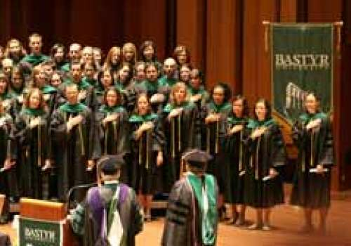 Bastyr students stand and cross their hearts as they read an oath at graduation.