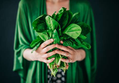 woman holding spinach