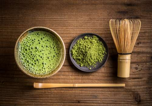 Cup of green tea on wooden table