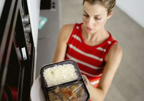 Woman contemplates whether or not her container is microwave safe.