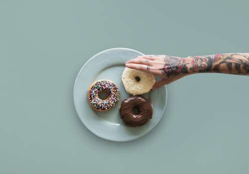 Person's hand reaching for donut on a plate