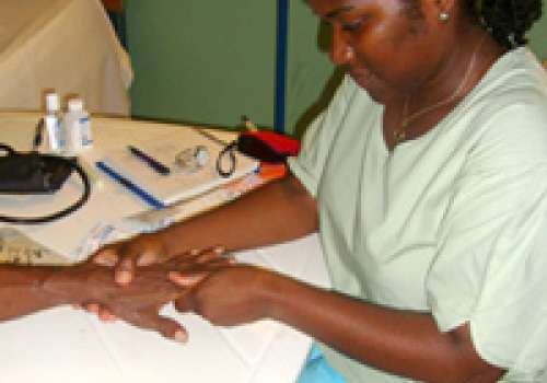Bastyr fellow Sabine Thomas examining the hand of a patient in Haiti