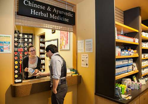 Employee helping customer at Chinese and Ayurvedic Herbal Medicine Dispensary.