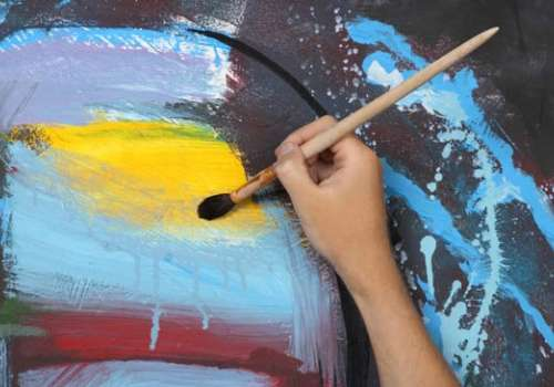 Hand holds paintbrush on abstract painting
