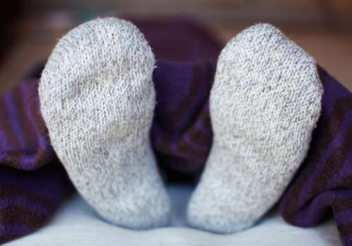Feet in thick socks under a blanket.