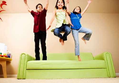 Children jumping on sofa.