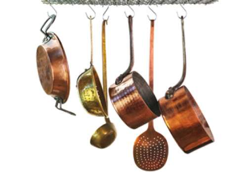 Copper cookware hanging from hooks.
